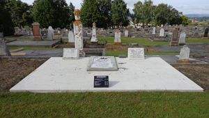 Waterblast clean surround, insert old cracked marble headstone into a concrete base and add black granite recumbent with same inscription